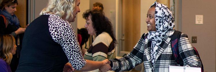 Recruiter and job seeker shaking hands at career fair
