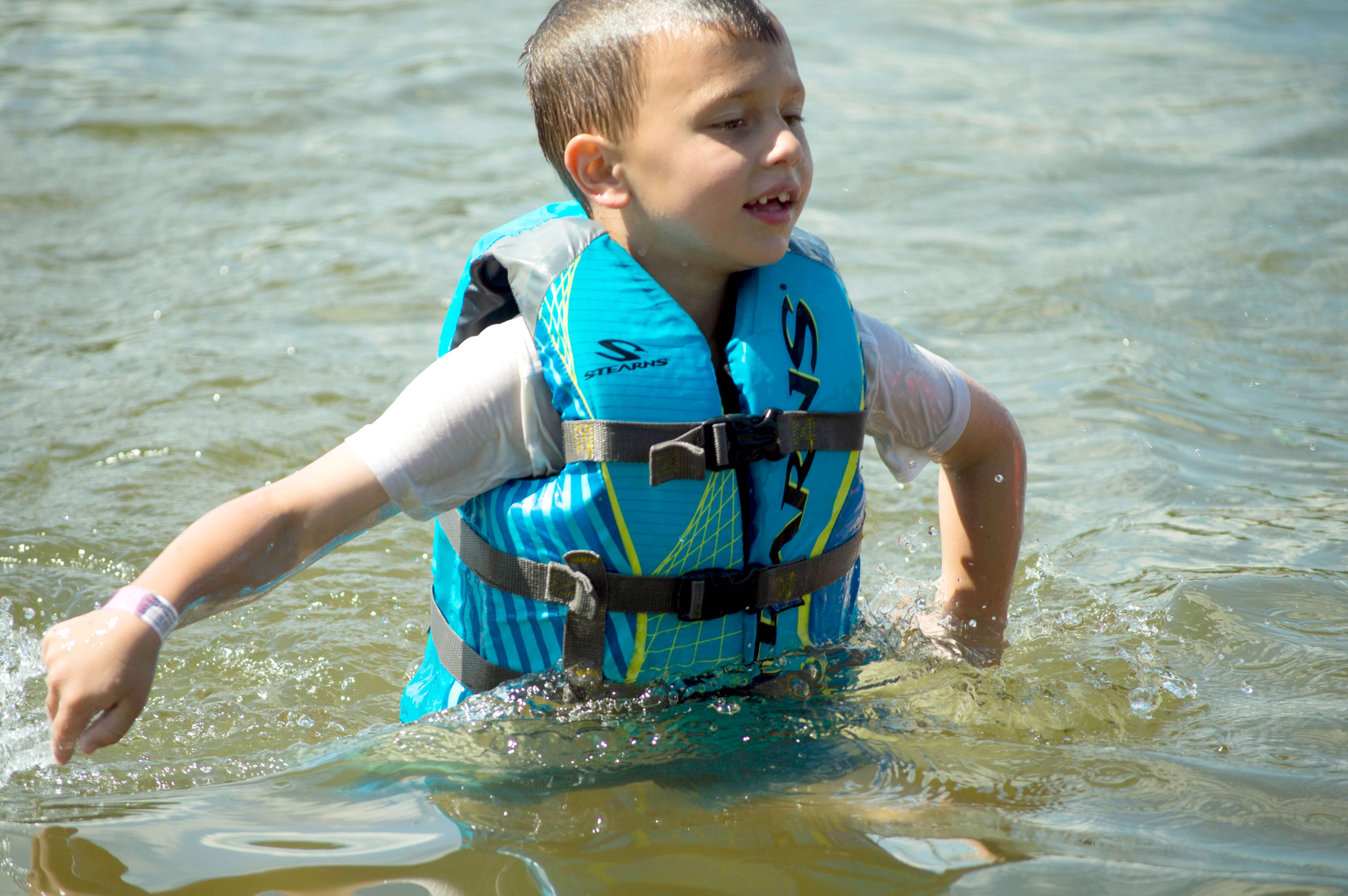 Boy wearing a life jacket swimming in Snail Lake.
