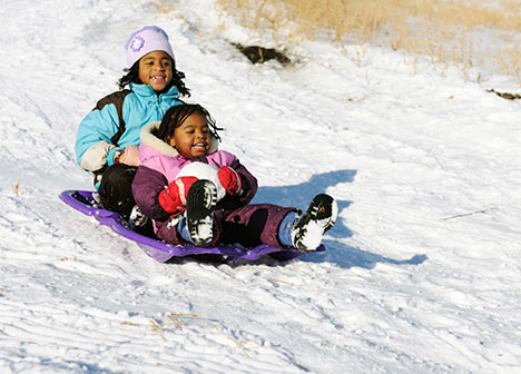 Two young girls on a sled