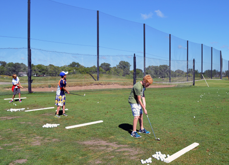 Junior golf camp participants on driving range