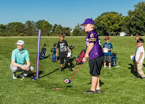 Keller instructor Jon Reigstad leading a golf lesson for five boys