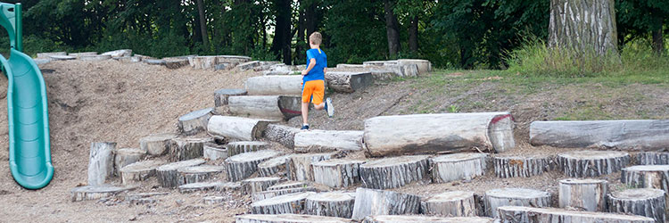 Boy running through the Lake Owasso nature play area