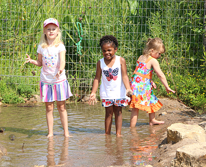 Day camp girls play at Discovery Hollow Nature Play Area