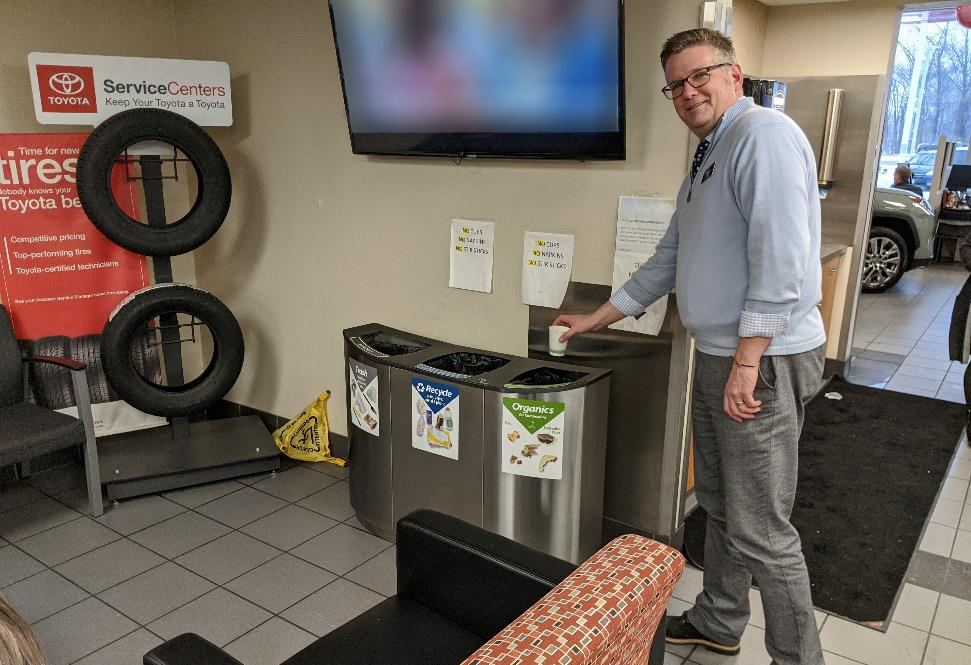 Man recycling a coffee cup at Maplewood Toyota