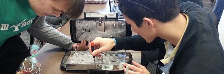 A volunteer fixer helps an attendee repair a waffle iron.