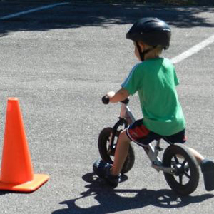 boy riding bike around traffic cone