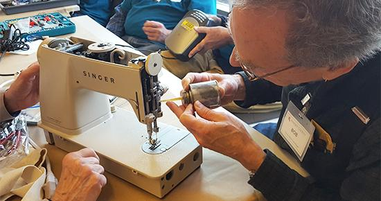 Volunteer fixing a sewing machine