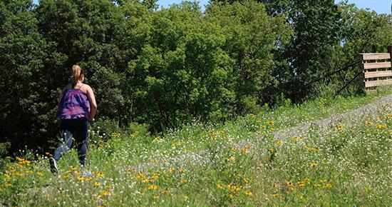 Girl walking on a nature path in the summer time
