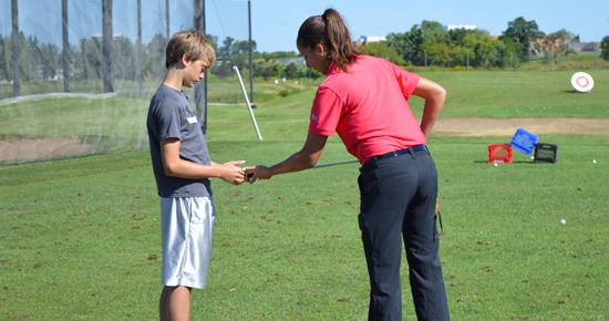 Golf instructor giving a lesson to a teenage boy