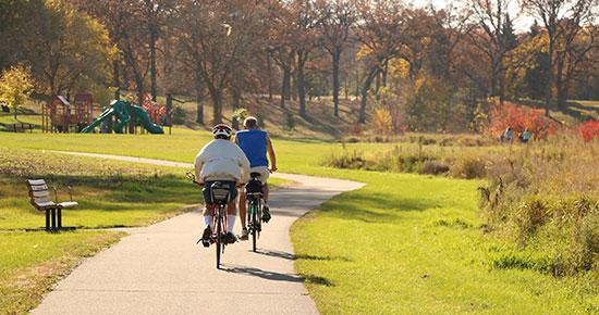 Two people biking at a park during the fall season.
