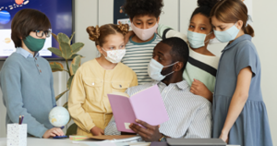 Group of elementary students in classroom wearing cloth face masks
