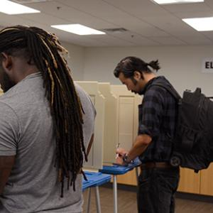 Voters filling in absentee ballots.