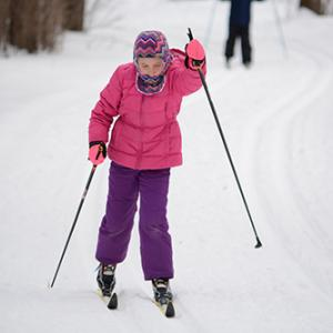 A girl cross-country skis at Tamarack Nature Center