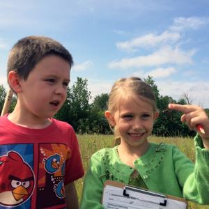 Boy and girl examining dragonfly