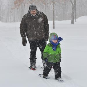 Adult and child snowshoeing at Tamarack Nature Center. Photo credit  Holly MacEwen.